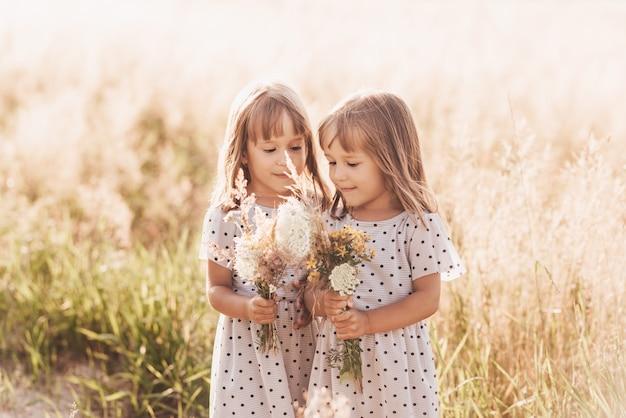 Duas garotinhas gêmeas idênticas felizes brincando juntos na natureza no verão. amizade de meninas e o conceito de juventude. estilo de vida de crianças ativas.