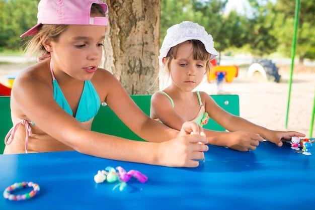 Duas garotinhas lindas brincando de bonecas ao ar livre enquanto relaxam na praia em um dia quente de verão