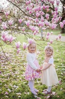 Duas garotinhas loiras de 3 anos de idade estão brincando no parque perto de uma magnólia em flor. beber chá. páscoa. primavera.