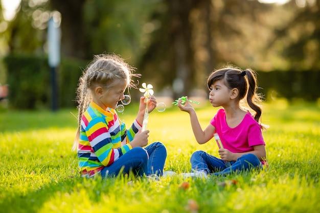 Duas garotinhas loiras e morena de verão sentadas no gramado soprando bolhas de sabão crianças de etnia europeia e indiana