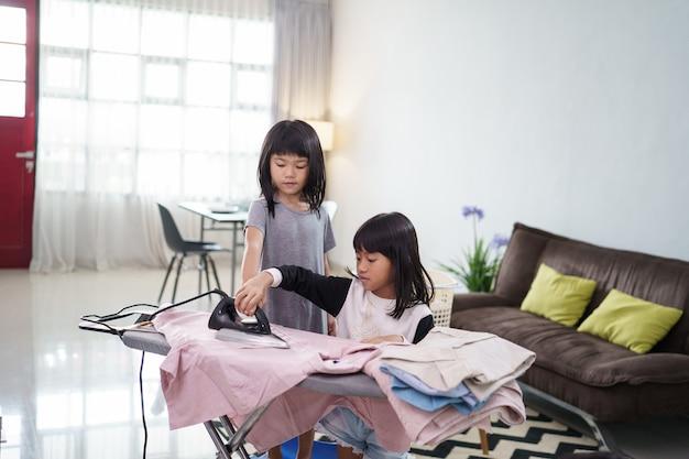 Duas garotinhas sorrindo alegremente enquanto passava roupas em casa