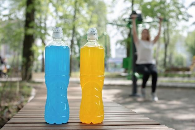 Duas garrafas azuis e laranja de bebida isotônica e uma mulher praticando esportes em um simulador ao ar livre, verão, fecham.