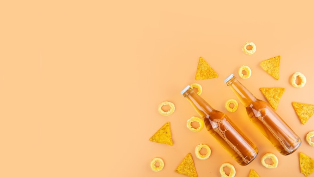 Duas garrafas de cerveja artesanal e cerveja porter e lanche de nachos e pistache em fundo bege. dia internacional da cerveja ou conceitos de octoberfest. foto minimalista. copie o espaço