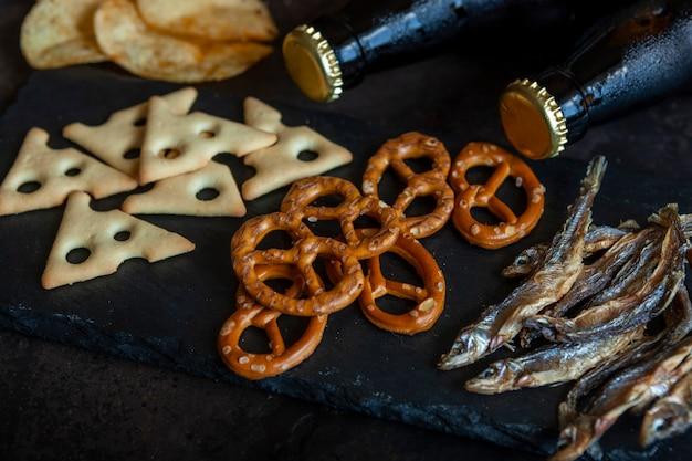 Duas garrafas de cerveja com batatas fritas, biscoitos salgados, pretzels e peixe seco
