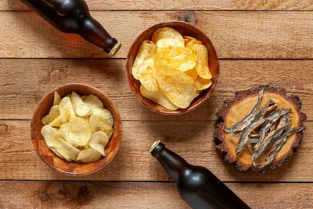 Duas garrafas de cerveja com batatas fritas e peixe seco