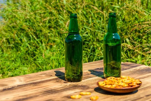 Duas garrafas de cerveja e prato de cerâmica com pretzels salgados na mesa de madeira rústica
