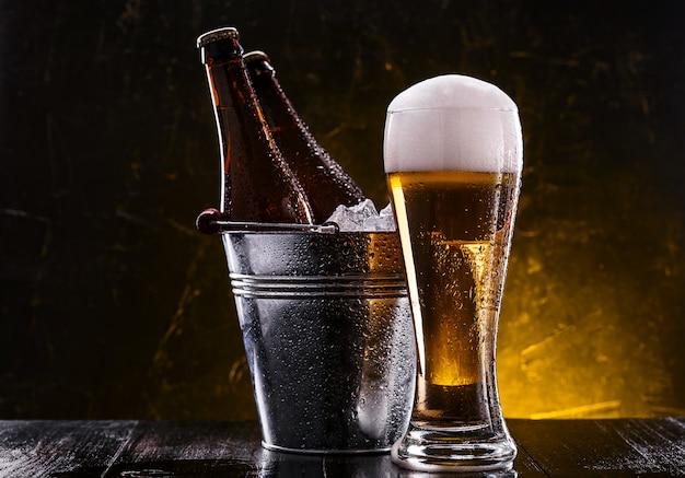 Duas garrafas de cerveja em um balde com gelo e um copo de cerveja com espuma exuberante