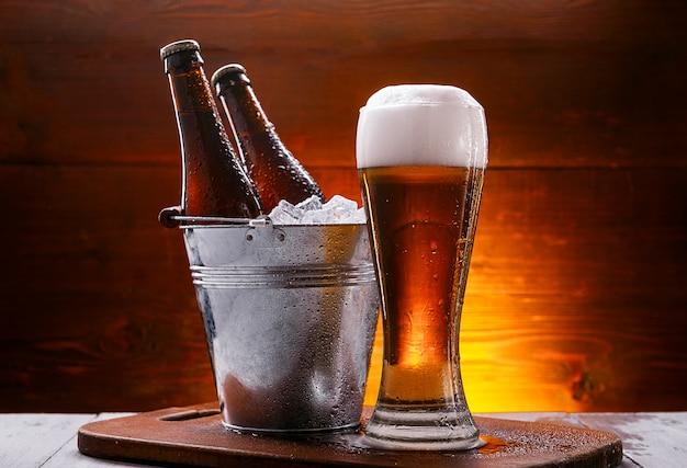 Duas garrafas de cerveja em um balde com gelo e um copo de cerveja com espuma exuberante Foto Premium