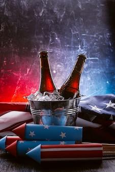 Duas garrafas de cerveja em um balde de gelo com a bandeira americana caída nas proximidades e foguetes para fogos de artifício. conceito de celebração do dia da independência