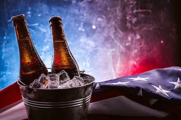 Duas garrafas de cerveja em um balde de gelo com a bandeira americana nas proximidades. conceito de celebração do dia da independência