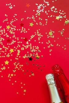 Duas garrafas de champanhe e confetes de glitter dourados. vista superior, close-up sobre fundo vermelho.