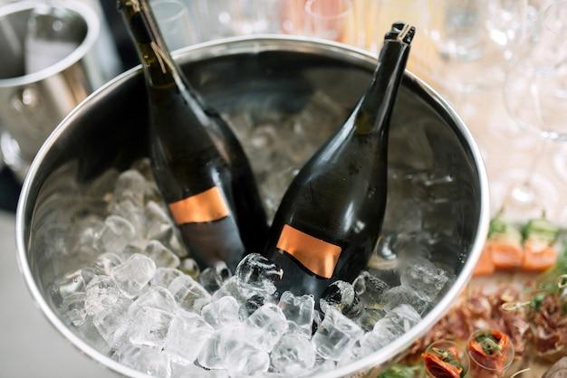 Duas garrafas de champanhe são resfriadas em um vaso com gelo.