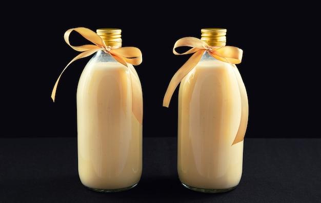 Duas garrafas de gemada caseira em fundo escuro