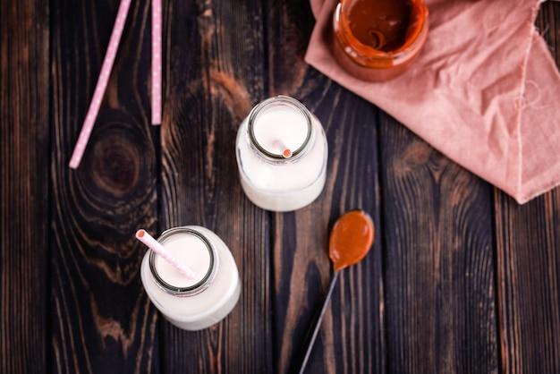 Duas garrafas de leite fresco com tubos e caramelo salgado caseiro fresco