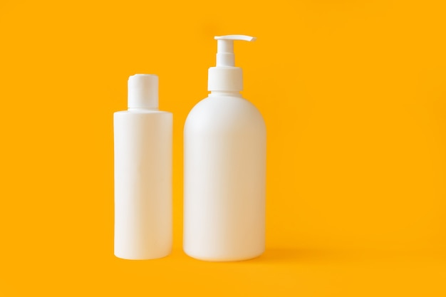 Duas garrafas de plástico brancas com gel e shampoo