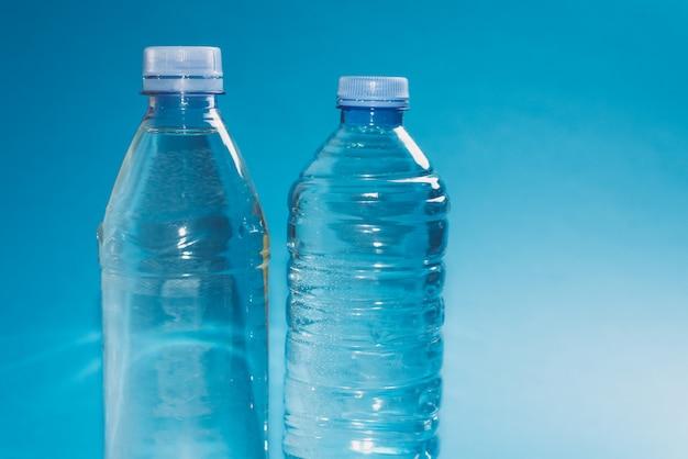 Duas garrafas de plástico diferentes com um brilho de água sobre uma superfície azul. copyspace, lugar para texto