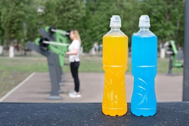 Duas garrafas de plástico laranja e azuis de bebida isotônica no fundo de um campo de esportes ao ar livre com equipamentos esportivos, verão, close-up.