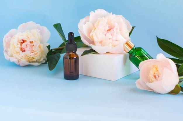Duas garrafas de vidro com óleos essenciais naturais em um pódio branco com uma flor de peônia. produto cosmético no pódio geométrico branco. produtos naturais orgânicos de autocuidado.