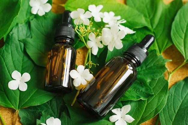 Duas garrafas de vidro de óleo cosmético encontram-se sobre um fundo de folhas verdes e flores brancas.