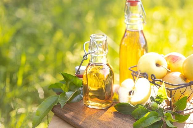 Duas garrafas de vidro de vinagre de maçã e maçãs frescas maduras.