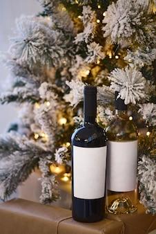 Duas garrafas de vinho com vinho tinto e branco perto da árvore de natal