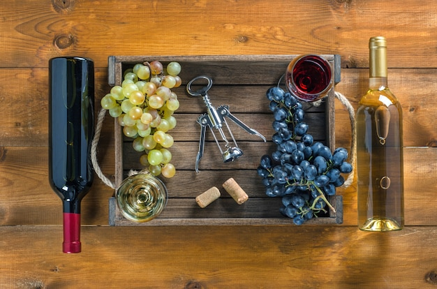 Duas garrafas de vinho e cacho de uvas em uma caixa com copos de vinho e um saca-rolhas no fundo de madeira. vista superior, cópia-espaço.