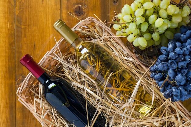 Duas garrafas de vinho na cesta com feno e cachos de uvas no fundo de madeira. vista de cima, estilo rústico.