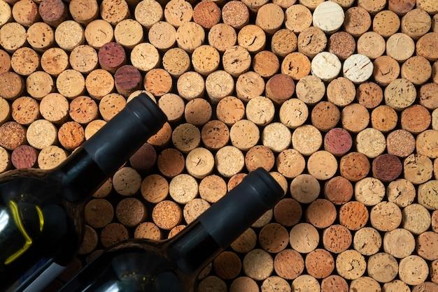 Duas garrafas de vinho repousam sobre rolhas de vinho, plano de fundo de design criativo, espaço para texto