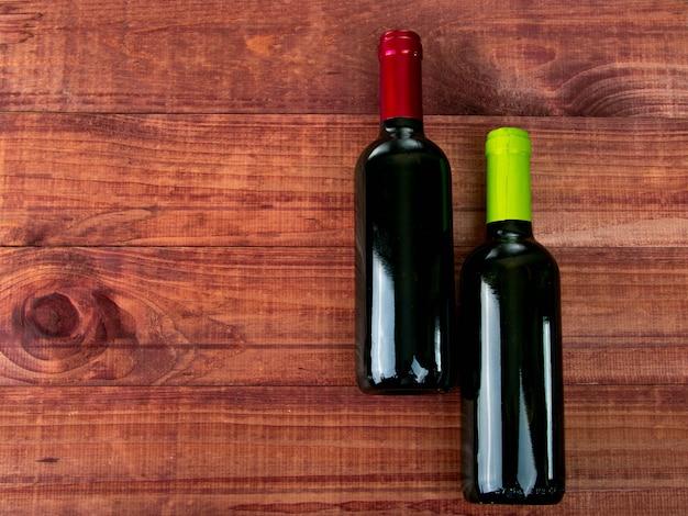 Duas garrafas de vinho. versões de bebidas em uma mesa de madeira.
