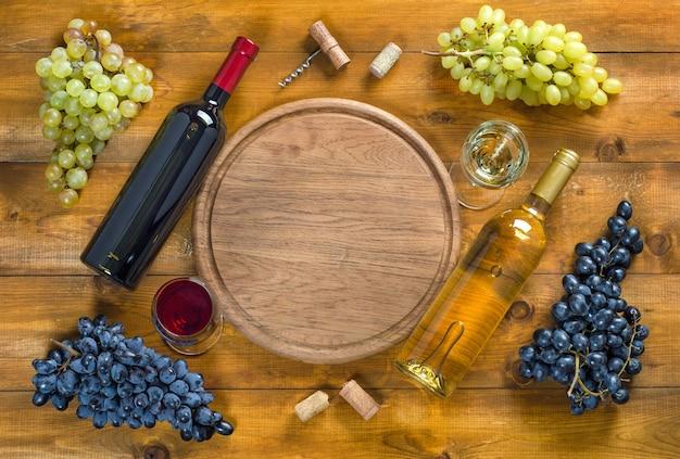 Duas garrafas e copos com vinho tinto e branco, cachos de uvas verdes e azuis, rolhas e saca-rolhas em fundo de madeira. vista superior, cópia-espaço, configuração plana.