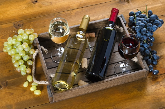 Duas garrafas e copos com vinho tinto e branco e uvas em um fundo de madeira. vista do topo.