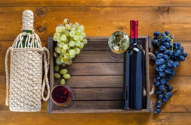 Duas garrafas e copos com vinho tinto e branco e uvas em um fundo de madeira. vista superior, cópia-espaço.