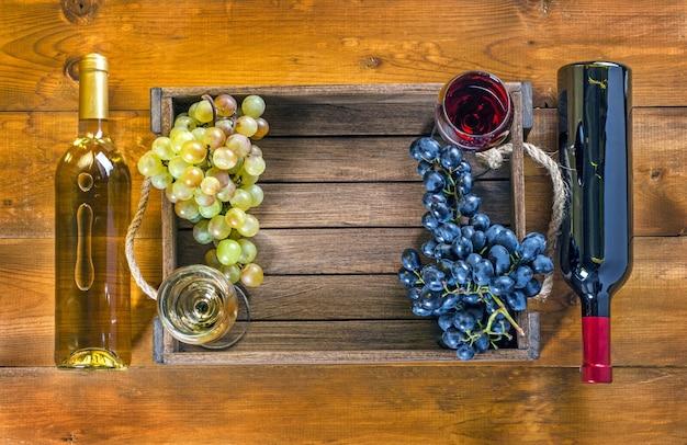 Duas garrafas e taças com vinho e uvas em um fundo de madeira. vista superior, cópia-espaço.