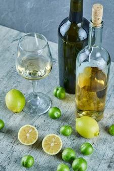Duas garrafas e um copo de vinho na mesa de mármore com limões e ameixas cereja
