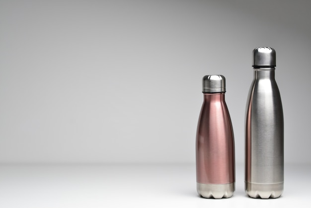 Duas garrafas térmicas de aço inoxidável isoladas em um fundo cinza cor prateada