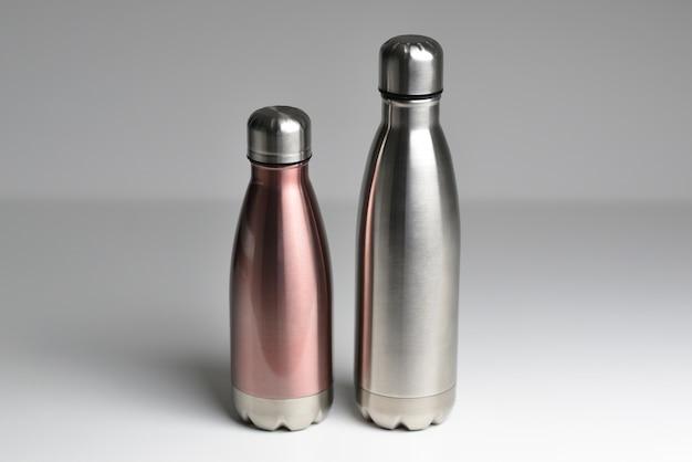 Duas garrafas térmicas de aço inoxidável isoladas no fundo branco cor prateada