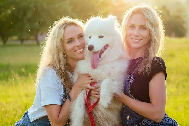 Duas gêmeas loiras lindas e charmosas, sorrindo, dentuça, de macacão jeans, estão sentadas com um cachorro samoiedo fofo branco, no parque de verão, ao fundo de raios de sol de vidro.