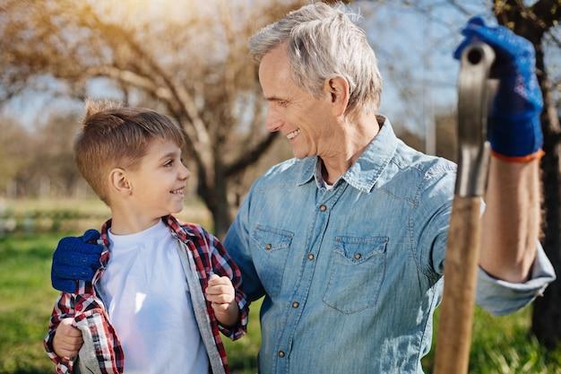 Duas gerações de homens passando tempo livre ao ar livre em um jardim e olhando um para o outro durante uma pausa