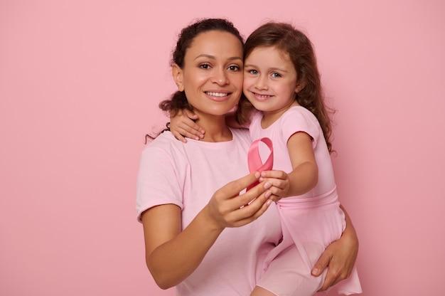 Duas gerações de mulheres, mulher e menina, mãe e filha posando contra um fundo rosa, segurando uma fita rosa, mostrando apoio e solidariedade aos pacientes e sobreviventes do câncer. conceitos médicos