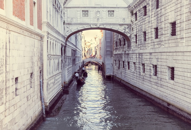 Duas gôndolas flutuam em um canal estreito em veneza