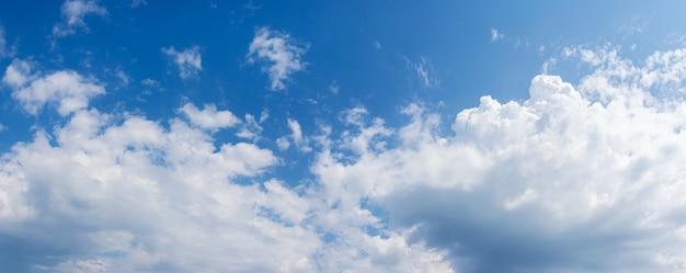 Duas grandes nuvens brancas no céu azul sob a luz do sol