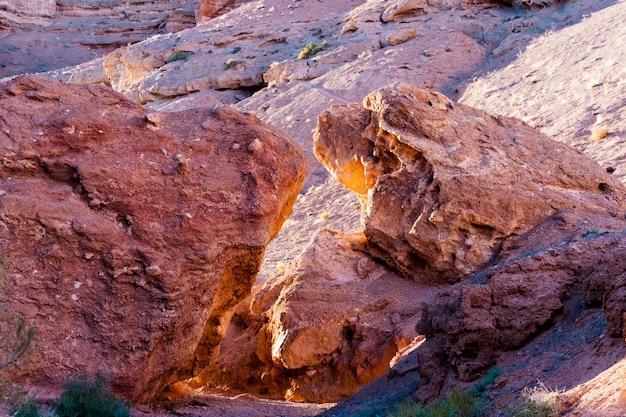 Duas grandes pedras das rochas vermelhas formam um arco e passam para o cânion de charyn. cazaquistão