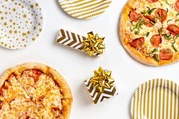 Duas grandes pizzas saborosas com calabresa e queijo em um prato branco e presentes