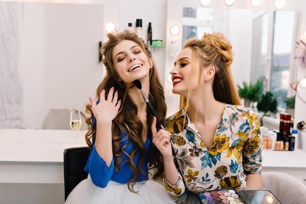 Duas incríveis modelos alegres se divertindo juntas no salão de cabeleireiro