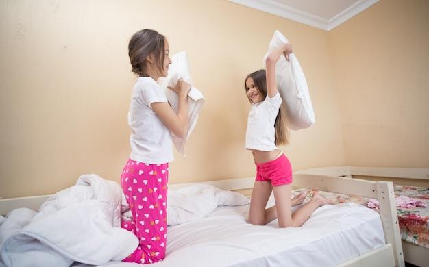 Duas irmãs adolescentes de pijama se divertindo em uma luta de travesseiros