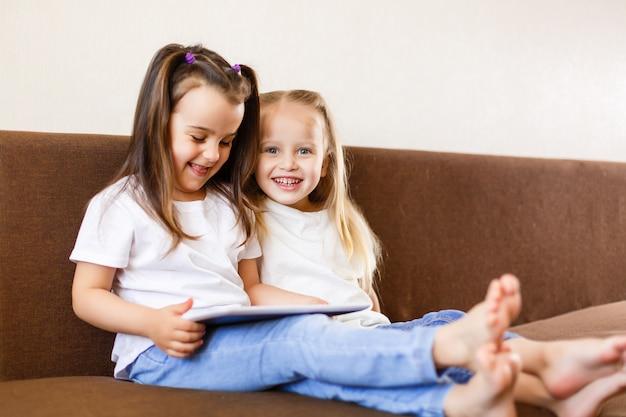 Duas irmãs adoráveis brincando com um tablet digital em casa sorrindo irmã com tablet pc