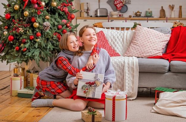 Duas irmãs alegres estão sentadas em casa perto da árvore de natal e olhando para caixas com presentes