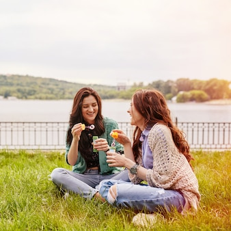 Duas irmãs alegres sentado na grama e soprando bolhas