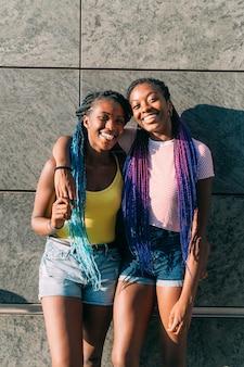 Duas irmãs ao ar livre posando abraçando sorrindo