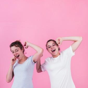 Duas irmãs bocejando contra fundo rosa
